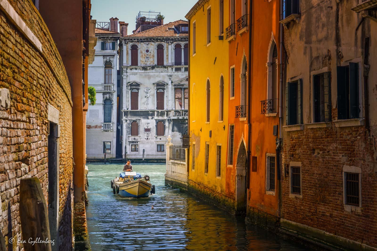 Båt i liten kanal i Venedig