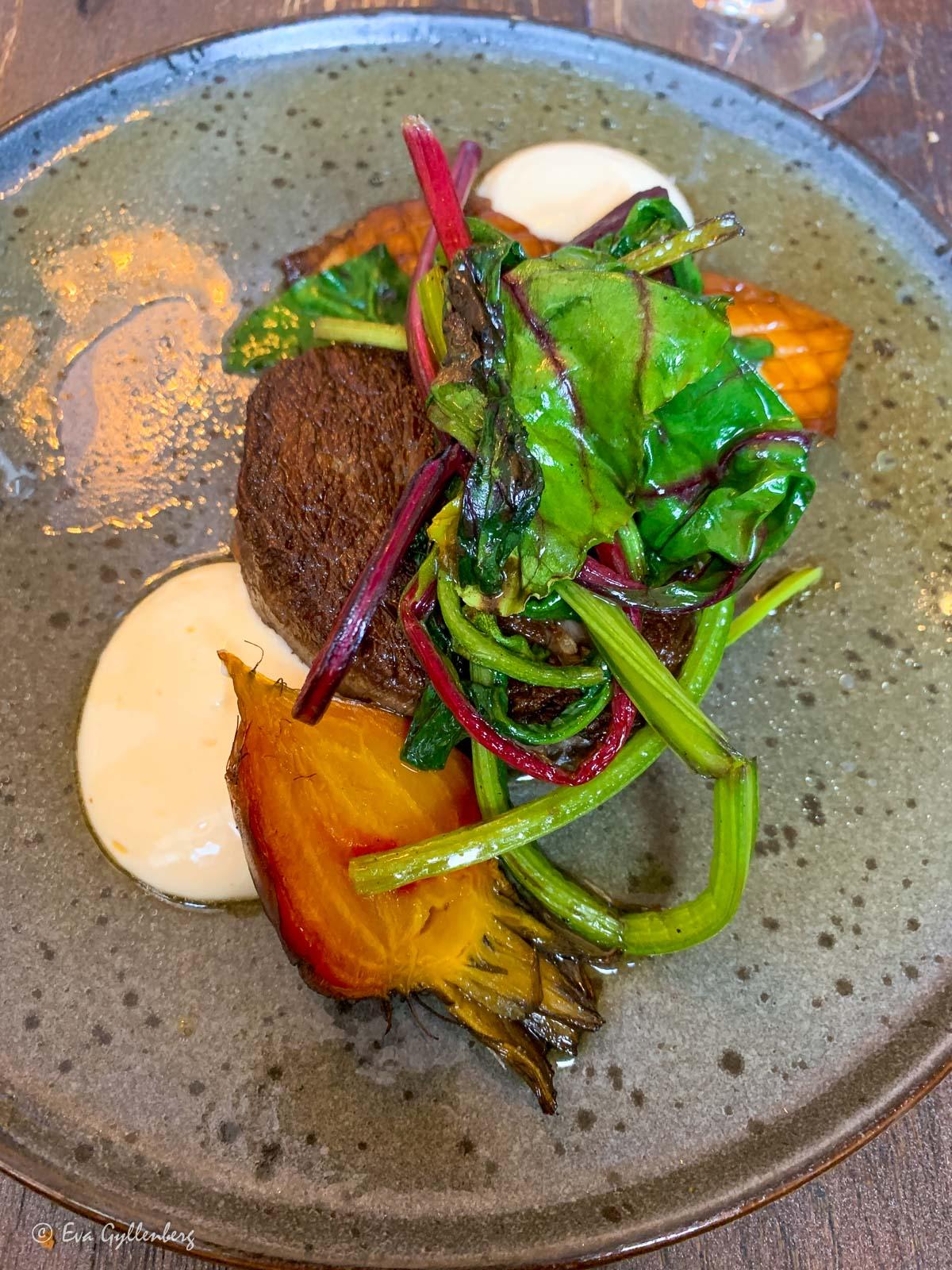 Köttbit med ugnsrostade grönsaker på restaurang i Lund
