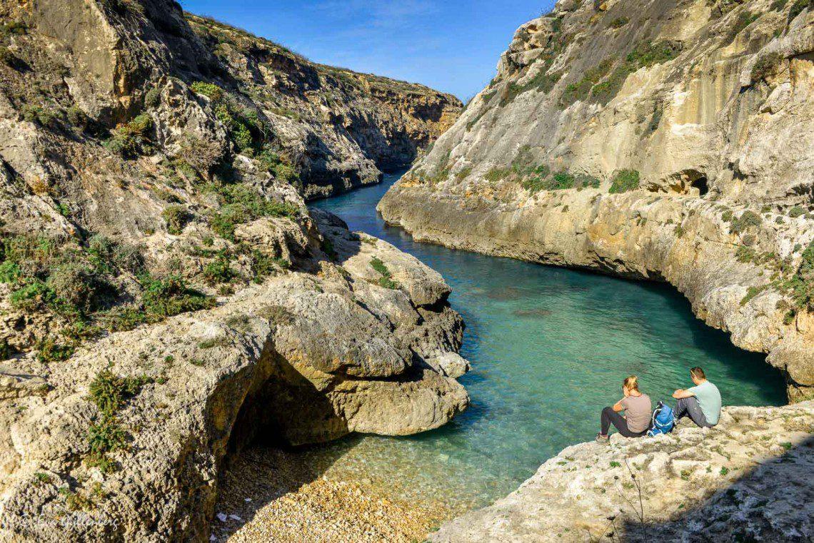 Två personer som tittar ut över viken Wied il-Ghasri på Gozo