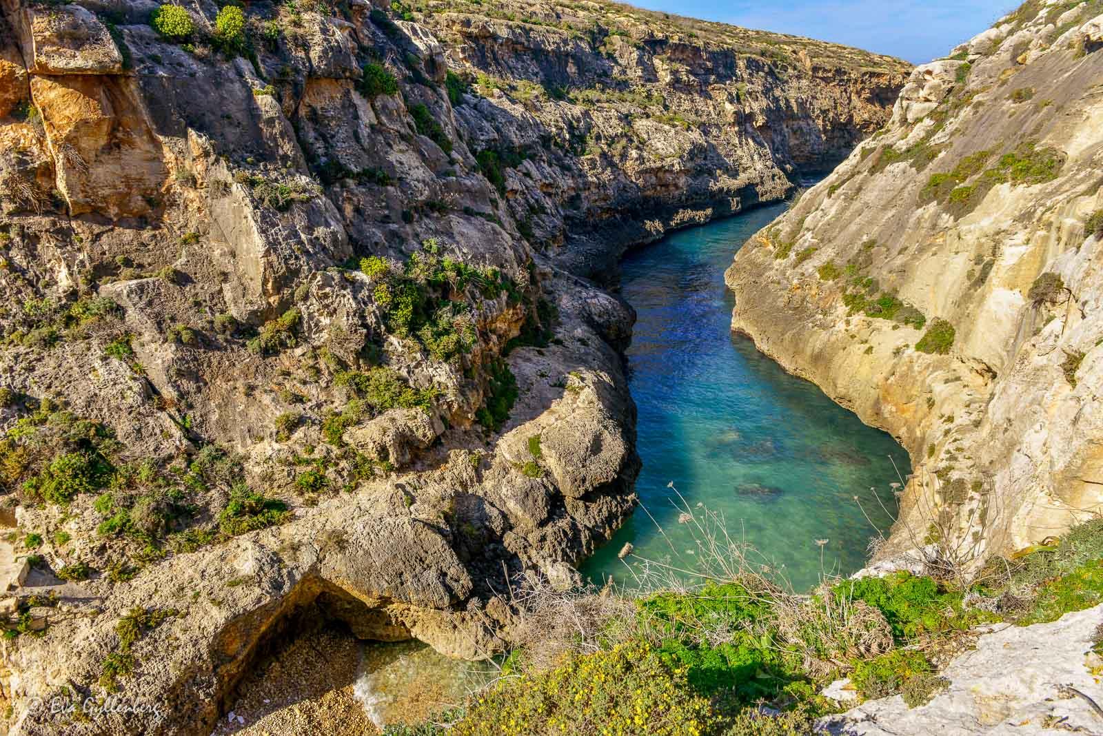 Smal vik med klippor och turkost hav