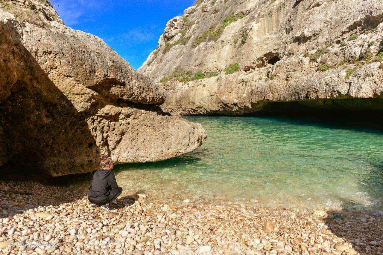 Tjej på stranden vid det turkosa vattnet i viken Wied il-Ghasri - Gozo