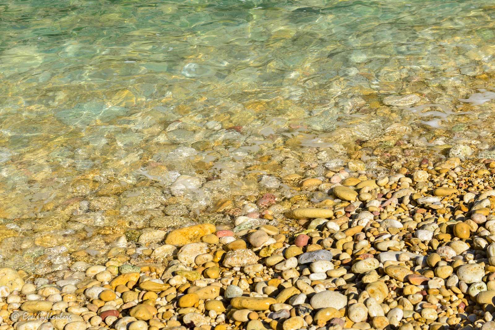 Klart turkost vatten och små gyllene stenar på stranden.