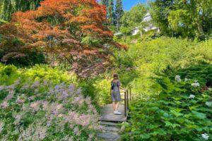 Kvinna i klänning på en bro i den japanska trädgården