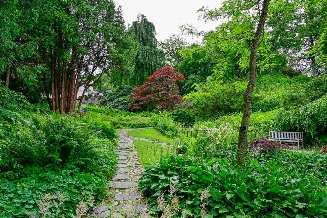 Stig i den japanska trädgården omgiven av färgglada lövträd