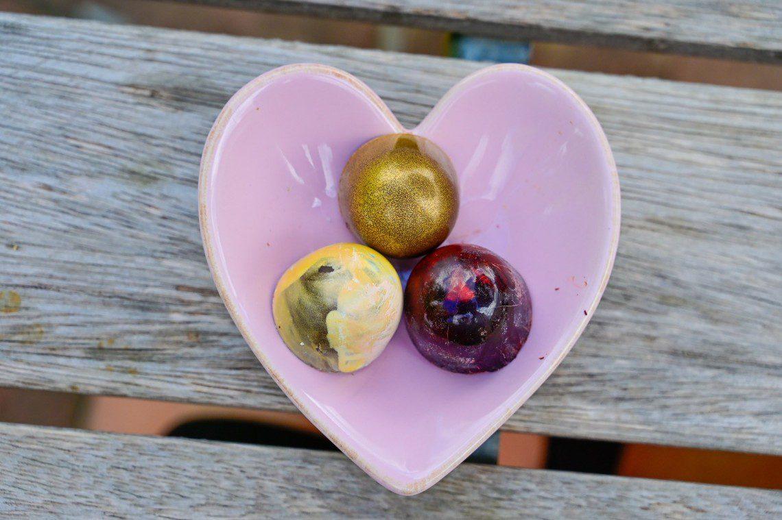 Tre praliner på ett hjärtformat fat