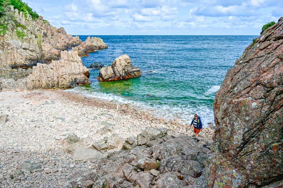 Stenig strand med blått hav