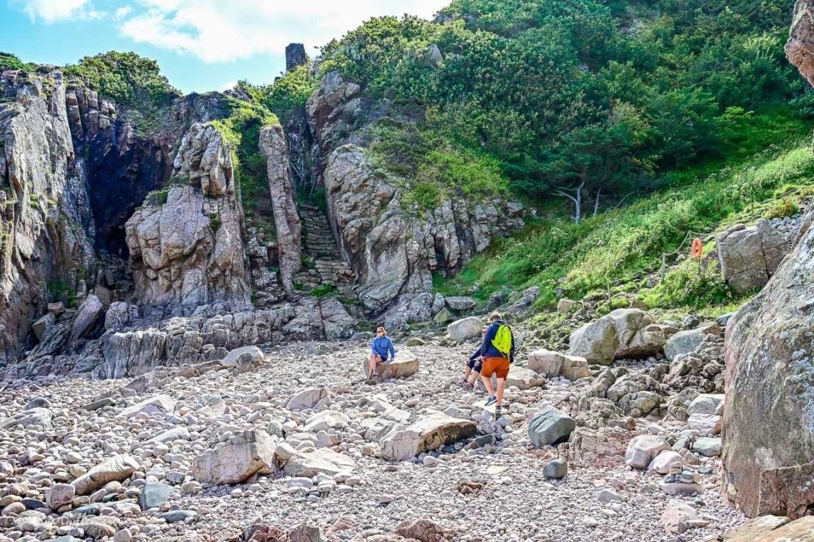 Människor sitter på en klippstrand vid Kullaberg