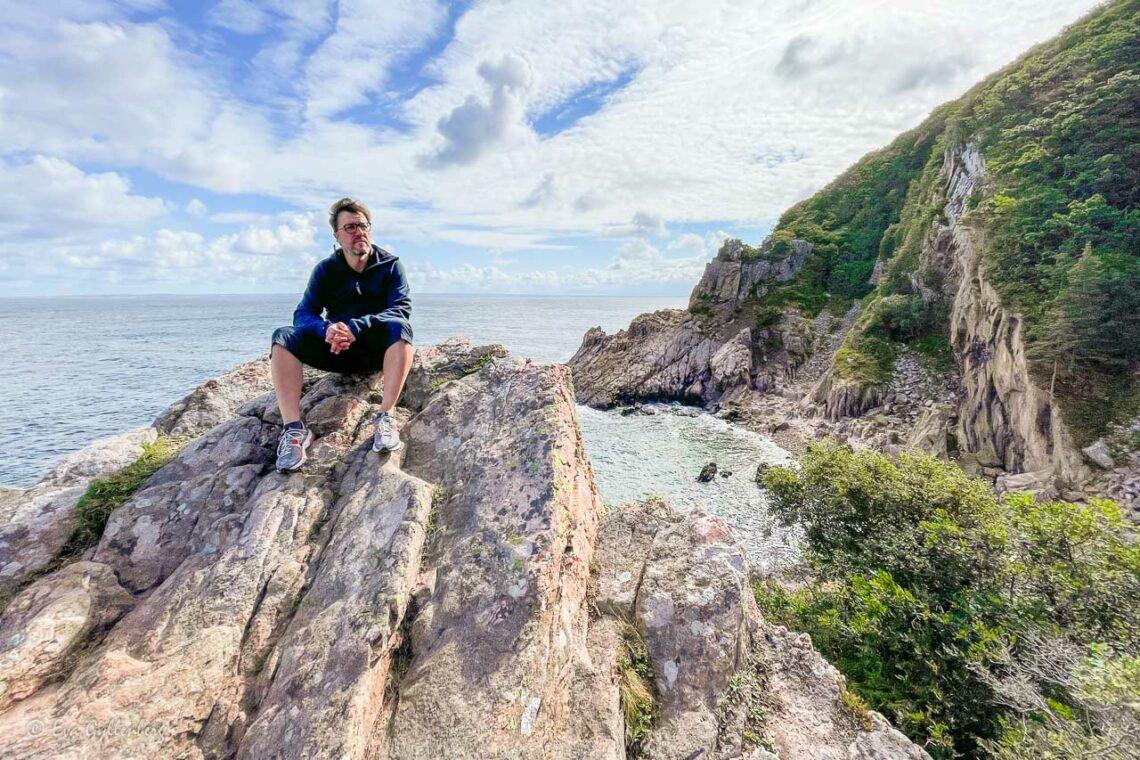 Man sitter på klippa högt över havet vid Skälderviken