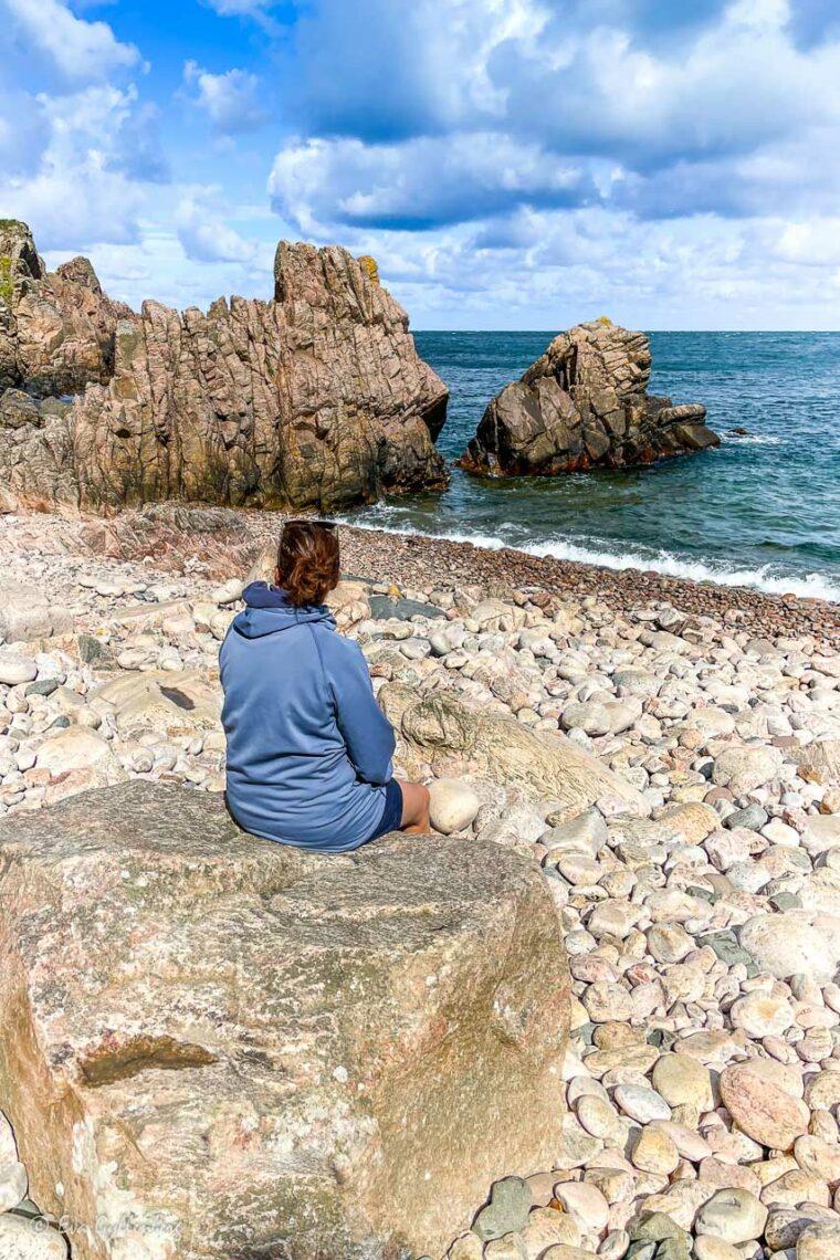 Kvinna sitter på stranden i solskenet