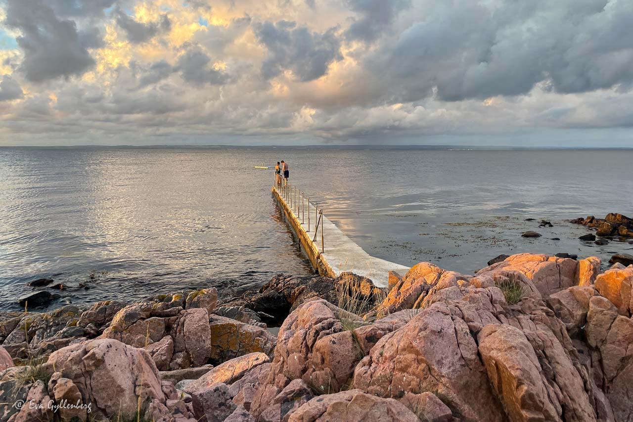 Badbryggan med badare med dramatisk himmel i Skäret